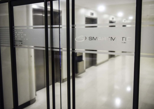 "Picture of the logo of Smartmatic, the firm that supplies Venezuela's voting technology, seen on a sliding door at the headquarters of the company in Caracas, on August 2, 2017. Smartmatic said official figures in Sunday's election of the new super-assembly, with candidates selected from the ruling party, were ""tampered with"" in such a way that the turnout appeared greater than it was. Venezuela's President Nicolas Maduro moved quickly Wednesday to swear in a new assembly with extraordinary powers as he faced charges that turnout figures for the body's election were ""manipulated."" / AFP PHOTO / Ronaldo SCHEMIDT"