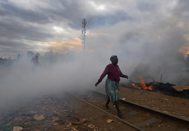 A woman walks past a shack which was burnt to the ground by protestors in the Kibera slum in Nairobi on August 12, 2017. Three people, including a child, have been shot dead in Kenya during opposition protests which flared for a second day Saturday after the hotly disputed election victory of President Uhuru Kenyatta. Demonstrations and running battles with police broke out in isolated parts of Nairobi slums after anger in opposition strongholds against August 8 election that losing candidate Raila Odinga claims was massively rigged. / AFP PHOTO / CARL DE SOUZA
