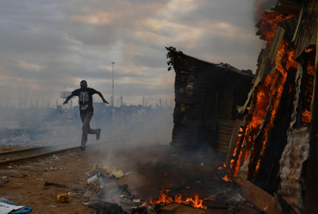 A man runs past a shack which was burnt to the ground by protestors in the Kibera slum in Nairobi on August 12, 2017. Three people, including a child, have been shot dead in Kenya during opposition protests which flared for a second day Saturday after the hotly disputed election victory of President Uhuru Kenyatta. Demonstrations and running battles with police broke out in isolated parts of Nairobi slums after anger in opposition strongholds against August 8 election that losing candidate Raila Odinga claims was massively rigged. / AFP PHOTO / CARL DE SOUZA