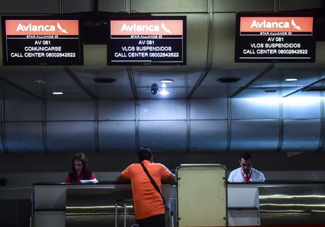 (FILES) This file photo taken on July 27, 2017 shows screens of Avianca Airline showing information of suspended flights at the airport of Maiquetia, Venezuela. A group of airlines have stopped flying to Venezuela since the the government owes them millions of dollars, and due to social unrest and insecurity, leaving the country increasingly isolated. / AFP PHOTO / RONALDO SCHEMIDT / TO GO WITH AFP STORY BY ALEXANDER MARTINEZ