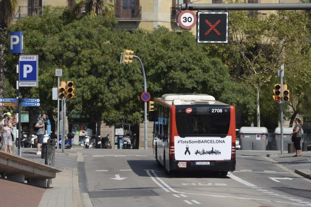 "A Barcelona city regular line bus with a message reading in Catalan ""We are all Barcelona"" waits at a junction in Barcelona on August 21, 2017. Spanish police said on August 21, 2017 that they have identified the driver of the van that mowed down pedestrians on the busy Las Ramblas boulevard in Barcelona, killing 13. The 22-year-old Moroccan is believed to be the last remaining member of a 12-man cell still at large in Spain or abroad, with the others killed by police or detained over last week's twin attacks in Barcelona and the seaside resort of Cambrils that claimed 14 lives, including a seven-year-old boy. / AFP PHOTO / Josep LAGO"