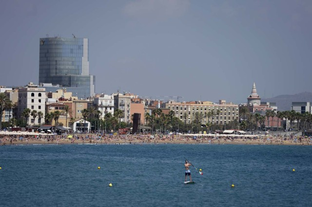 A general view taken on August 21, 2017 shows the Barceloneta beach of Barcelona with tourists and residents enjoying a sunny day four days after the Barcelona and Cambrils attacks that killed 15 people. Spanish police said on August 21, 2017 that they have identified the driver of the van that mowed down pedestrians on the busy Las Ramblas boulevard in Barcelona, killing 13. The 22-year-old Moroccan is believed to be the last remaining member of a 12-man cell still at large in Spain or abroad, with the others killed by police or detained over last week's twin attacks in Barcelona and the seaside resort of Cambrils that claimed 14 lives, including a seven-year-old boy. / AFP PHOTO / Josep LAGO