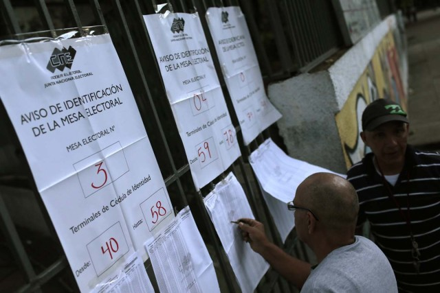 People check electoral lists before voting during the Constituent Assembly election in Caracas, Venezuela, July 30, 2017. REUTERS/Marco Bello