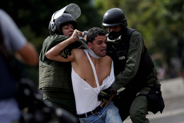 FILE PHOTO: A demonstrator is detained at a rally during a strike called to protest against Venezuelan President Nicolas Maduro's government in Caracas, Venezuela, July 27, 2017 . REUTERS/Ueslei Marcelino/File Photo