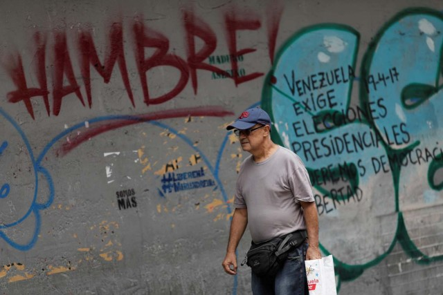 """A man walks past of a wall with graffiti that reads """"hungry"""", in Caracas, Venezuela August 3, 2017. REUTERS/Ueslei Marcelino"""