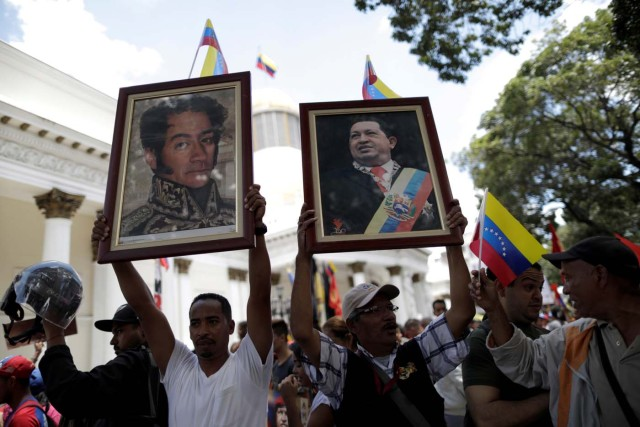Supporters of Venezuela's President Nicolas Maduro's government hold pictures of late Venezuela's President Hugo Chavez and Venezuela's national hero Simon Bolivar as they demonstrate before the first session of the constituent assembly in Caracas, Venezuela August 4, 2017. REUTERS/Ueslei Marcelino