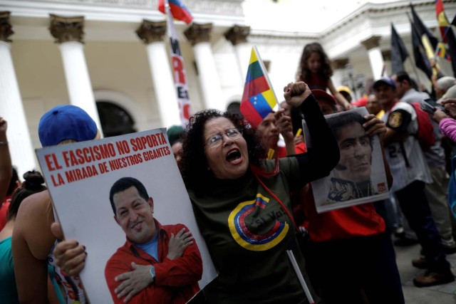 "Supporters of Venezuela's President Nicolas Maduro's government demonstrate before the first session of constituent assembly in Caracas, Venezuela August 4, 2017. The poster with late Venezuela's President Hugo Chavez reads: ""Fascism does not stand the gaze of our giants."" REUTERS/Ueslei Marcelino"