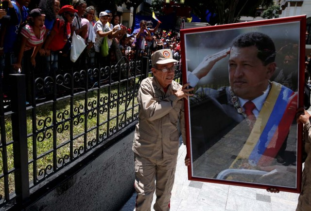 Members of the militia carry a picture of Venezuela's late President Hugo Chavez outside Palacio Federal Legislativo during the National Constituent Assembly's first session, in Caracas, Venezuela August 4, 2017. REUTERS/Carlos Garcia Rawlins