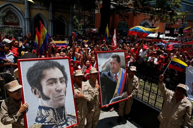 Members of the militia carry a picture of Venezuela's late President Hugo Chavez and Venezuela's national hero Simon Bolivar outside Palacio Federal Legislativo during the National Constituent Assembly's first session, in Caracas, Venezuela August 4, 2017. REUTERS/Carlos Garcia Rawlins