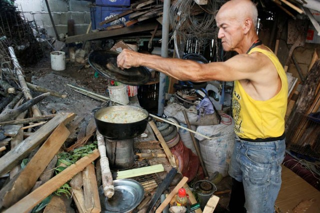 Ipolito Gutierrez cooks the meal using firewood at his house in San Cristobal, Venezuela August 3, 2017. Picture taken August 3, 2017. REUTERS/Luis Parada