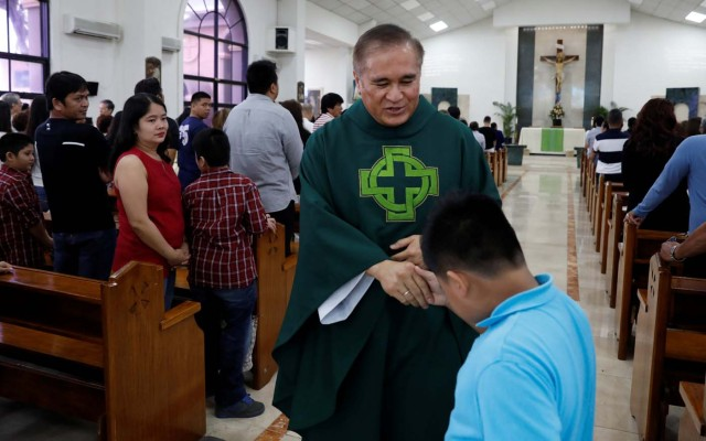 Roman Catholic priest Monsignor James Benavente gives a blessing to a boy after a Sunday mass at Sta Barbara Church on the island of Guam, a U.S. Pacific Territory, August 13, 2017.  REUTERS/Erik De Castro
