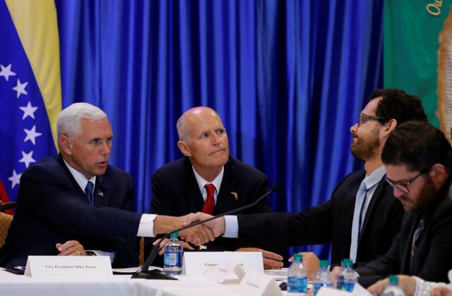 U.S. Vice President Mike Pence shakes hands with former prisoner Francisco Marquez after hearing his story as meets with members of the Venezuelan exile community, recent Venezuelan migrants, other local leaders and officials about the continuing devastation and unrest in Venezuela at Our Lady of Guadalupe Catholic Church in Doral, Florida, August 23, 2017. Florida Gov. Rick Scott is in center. REUTERS/Joe Skipper
