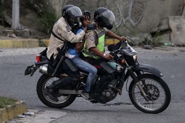 VEN32. CARACAS (VENEZUELA), 24/06/2017 - Fuerzas de seguridad detienen a un manifestante durante una protesta hoy, sábado 24 de junio de 2017, en Caracas (Venezuela). Los cuerpos de seguridad de Venezuela dispersaron hoy con gases lacrimógenos una manifestación que la oposición realizaba ante la base militar La Carlota, frente a la cual un joven fue asesinado el pasado jueves y a cuyos jardines decenas de manifestantes ingresaron este sábado, según constató Efe. EFE/Miguel Gutiérrez