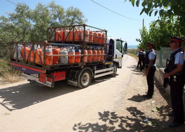 Un camión (i) retira parte de las 120 bombonas de butano halladas en el chalet de Alcanar Platja utilizado por los terroristas de Barcelona y Cambrils