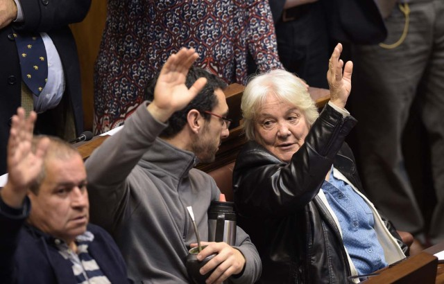 Uruguay's new vice-president Lucia Topolansky (R) raises her hand to vote before her swearing-in ceremony in Montevideo, on September 13, 2017. Topolansky replaces Raul Sendic, who resigned on Saturday over allegations he used public money for personal shopping. / AFP PHOTO / MIGUEL ROJO