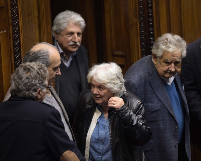 Uruguay's new vice-president Lucia Topolansky (C), accompanied by her husband, senator and former president Jode Mujica (R), talk with fellow lawmakers after her swearing-in ceremony in Montevideo, on September 13, 2017. Topolansky replaces Raul Sendic, who resigned on Saturday over allegations he used public money for personal shopping. / AFP PHOTO / MIGUEL ROJO