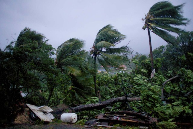 "A picture taken on September 19, 2017 shows the powerful winds and rains of hurricane Maria battering the city of Petit-Bourg on the French overseas Caribbean island of Guadeloupe. Hurricane Maria strengthened into a ""potentially catastrophic"" Category Five storm as it barrelled into eastern Caribbean islands still reeling from Irma, forcing residents to evacuate in powerful winds and lashing rain. / AFP PHOTO / Cedrik-Isham Calvados /"