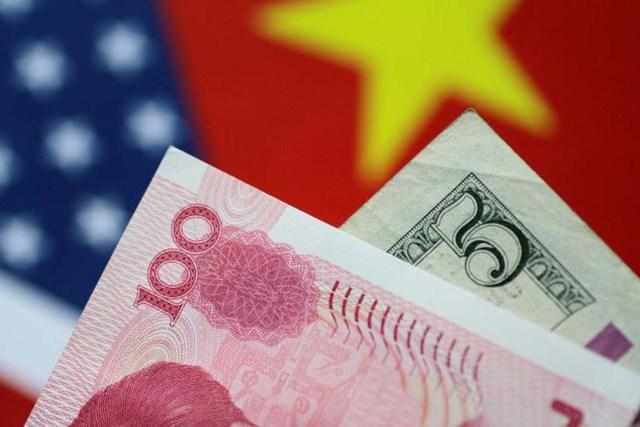 En la imagen de archivo se ven 5 dólares estadounidenses y 100 yuan de China, el 2 de junio de 2017. REUTERS/Thomas White/Illustration - RTX38MK7