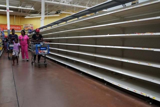 People walk past empty shelves where bread is normally sold in a Walmart store in advance of Hurricane Irma's expected arrival in North Miami Beach, Florida, U.S., September 7, 2017. REUTERS/Carlo Allegri