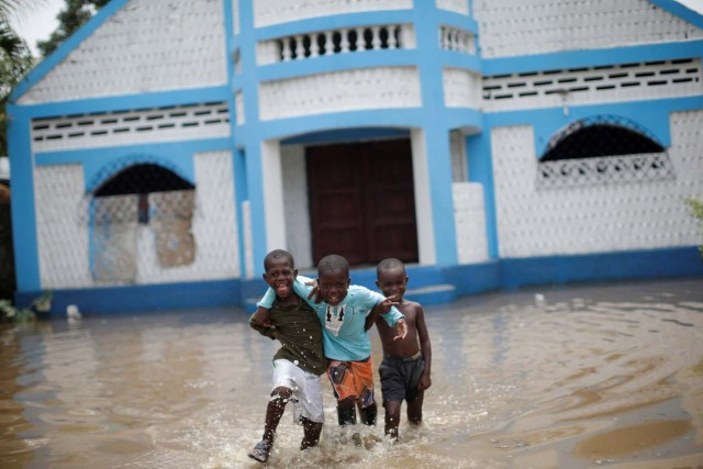 Boys gesture to the camera as they walk in a flooded area after hurricane Irma in Fort Liberte, Haiti September 8, 2017. REUTERS/Andres Martinez Casares