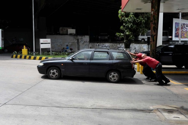 Gas station attendants push a car at a gas station of Venezuelan state-owned oil company PDVSA in Caracas, Venezuela September 21, 2017. REUTERS/Marco Bello