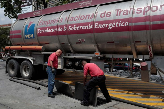 Workers set up a fuel tank truck for unloading gasoline at a gas station of Venezuelan state-owned oil company PDVSA in Caracas, Venezuela September 21, 2017. REUTERS/Marco Bello