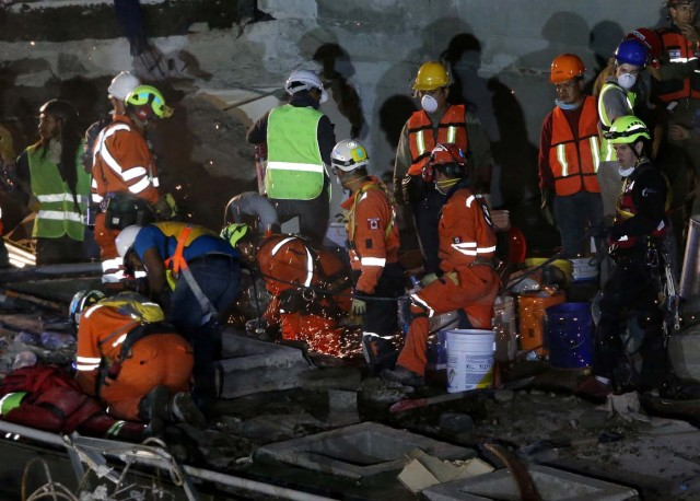 Members of rescue teams search for survivors in the rubble of a collapsed building after an earthquake in Mexico City, Mexico September 23, 2017. REUTERS/Henry Romero