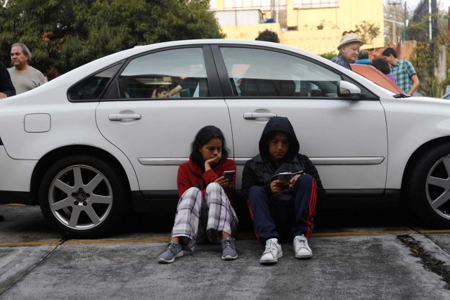A couple protects themselves in a car inside a residential area after a tremor was felt in Mexico City, Mexico, September 23, 2017. REUTERS/Edgard Garrido