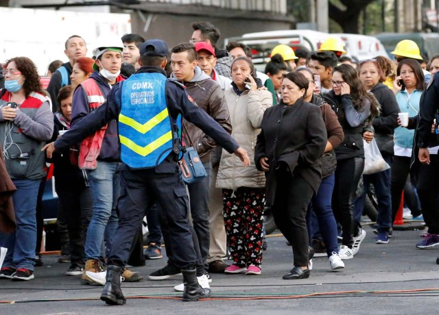 A police officer and people wait along the street after a tremor was felt in Mexico City, Mexico September 23, 2017. REUTERS/Henry Romero