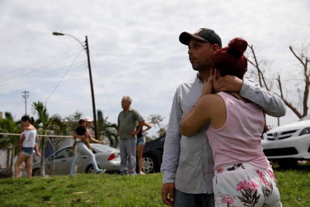 Local residents react while they look at the water flowing over the road at the dam of the Guajataca lake after the area was hit by Hurricane Maria in Guajataca, Puerto Rico September 23, 2017. REUTERS/Carlos Garcia Rawlins