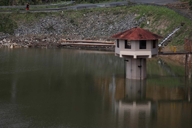 People walk next to a water level tower of the dam at the Guajataca lake after the area was hit by Hurricane Maria in Guajataca, Puerto Rico September 23, 2017. REUTERS/Carlos Garcia Rawlins