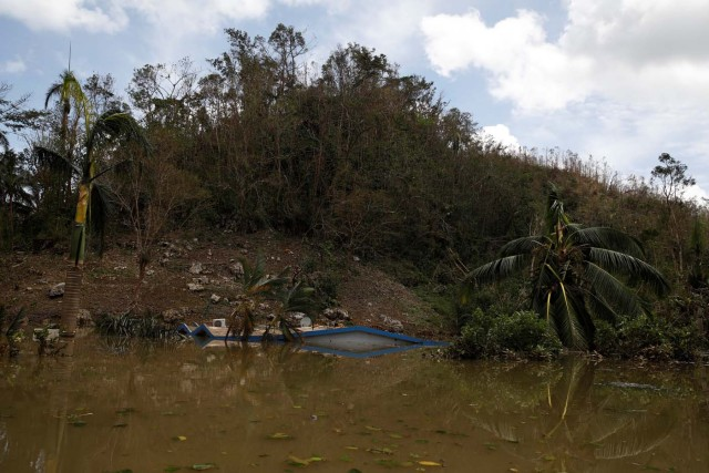 The roof of a house submerged by flood waters is seen close to the dam of the Guajataca lake after the area was hit by Hurricane Maria in Guajataca, Puerto Rico September 23, 2017. REUTERS/Carlos Garcia Rawlins