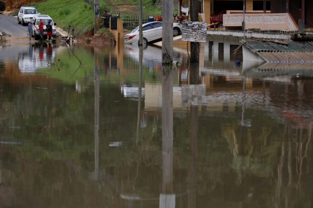 Local residents look at houses submerged by flood waters close to the dam of the Guajataca lake after the area was hit by Hurricane Maria in Guajataca, Puerto Rico September 23, 2017. REUTERS/Carlos Garcia Rawlins