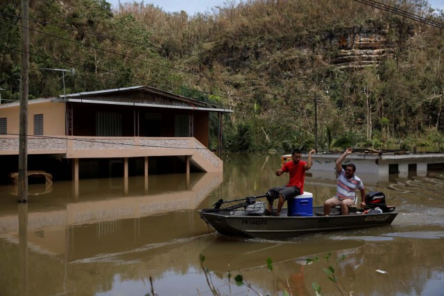Local residents use a boat to pass next to a flooded houses close to the dam of the Guajataca lake after the area was hit by Hurricane Maria in Guajataca, Puerto Rico September 23, 2017. REUTERS/Carlos Garcia Rawlins