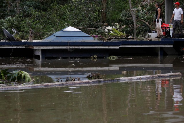Men stand at the roof of a house submerged by flood waters close to the dam of the Guajataca lake after the area was hit by Hurricane Maria in Guajataca, Puerto Rico September 23, 2017. REUTERS/Carlos Garcia Rawlins