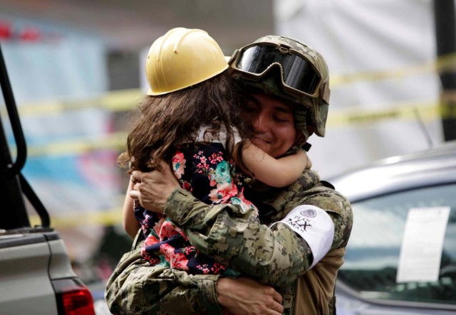 A girl hugs a Mexican marine officer as she offers hugs to people near the site of a collapsed building after an earthquake, in Mexico City, Mexico September 23, 2017. REUTERS/Jose Luis Gonzalez TPX IMAGES OF THE DAY