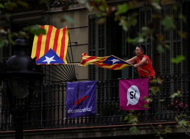 Una mujer agita banderas separatistas catalanas durante una manifestación en favor del referéndum de independencia del 1 de octubre prohibido en Barcelona, España el 28 de septiembre de 2017. REUTERS/Juan Medina