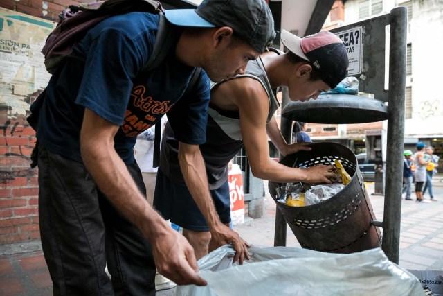 """ACOMPAÑA CRÓNICA: VENEZUELA CRISIS. CAR05. CARACAS (VENEZUELA), 25/09/2017.- Fotografía fechada el 20 de septiembre de 2017 que muestra a dos hombres mientras hurgan en una basura en busca de comida en una calle de Caracas (Venezuela). En las calles de Caracas deambulan cada vez más niños y de menos edad. Se trata, según analistas y activistas de derechos humanos, de una nueva oleada de pequeños que prácticamente han abandonado sus hogares, aunque esta vez la razón es una sola: """"La falta de comida en sus casas"""". EFE/Miguel Gutiérrez"""