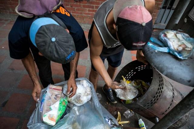 """ACOMPAÑA CRÓNICA: VENEZUELA CRISIS. CAR04. CARACAS (VENEZUELA), 25/09/2017.- Fotografía fechada el 20 de septiembre de 2017 que muestra a dos hombres mientras hurgan en una basura en busca de comida en una calle de Caracas (Venezuela). En las calles de Caracas deambulan cada vez más niños y de menos edad. Se trata, según analistas y activistas de derechos humanos, de una nueva oleada de pequeños que prácticamente han abandonado sus hogares, aunque esta vez la razón es una sola: """"La falta de comida en sus casas"""". EFE/Miguel Gutiérrez"""