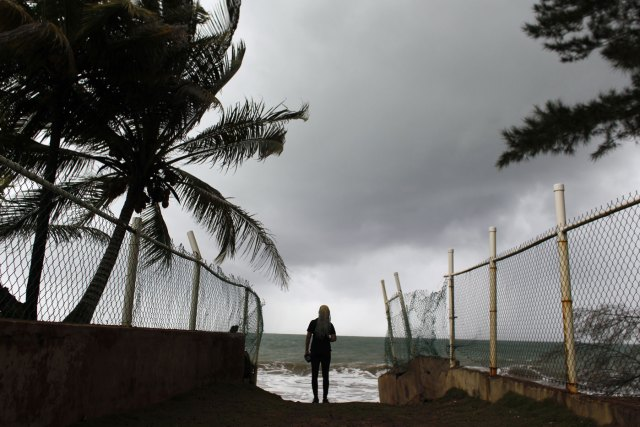 woman looks at heavy surf as Hurricane Irma approaches Puerto Rico in Luquillo, on September 6, 2017. Irma is expected to reach the Virgin Islands and Puerto Rico by nightfall on September 6.