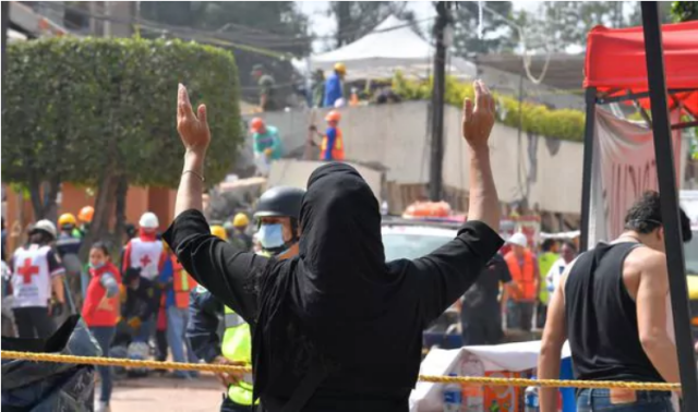 La súplica de una mujer durante la búsqueda de sobrevivientes en el derrumbe del colegio en la Ciudad de México (AFP PHOTO / Omar TORRES)