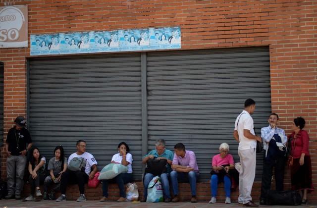 People wait to board a bus at a bus in Caracas on October 11, 2017 as scores of disappointed Venezuelans who see no end to the crisis choose to leave the country. Venezuela, which holds regional elections on October 15, is a country at the top of the Latin American continent that is in deep economic and political crisis. / AFP PHOTO / Federico PARRA