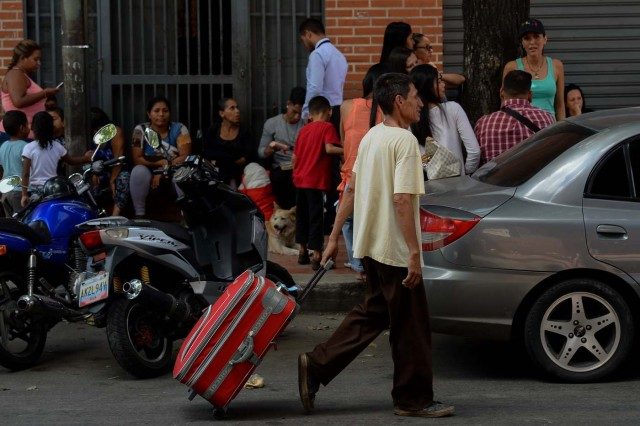 A man carries the suitcase of a passenger at a bus station in Caracas on October 11, 2017 as scores of disappointed Venezuelans who see no end to the crisis choose to leave the country. Venezuela, which holds regional elections on October 15, is a country at the top of the Latin American continent that is in deep economic and political crisis. / AFP PHOTO / Federico PARRA