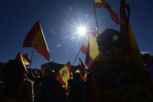 La gente agita banderas españolas durante una manifestación llamando a la unidad en Madrid el 28 de octubre de 2017, un día después de que se impuso el control directo sobre Cataluña en un intento por separarse de España. España se movió para afirmar el dominio directo sobre Cataluña, reemplazando a sus funcionarios ejecutivos y altos para sofocar un impulso de independencia que ha sumido al país en una crisis y ha puesto nerviosa a la Europa secesionista. / AFP PHOTO / JAVIER SORIANO