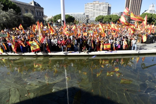 La gente agita banderas españolas durante una manifestación llamando a la unidad en la Plaza de Colón en Madrid el 28 de octubre de 2017, un día después de que se impuso el control directo sobre Cataluña en un intento por separarse de España. España se movió para afirmar el dominio directo sobre Cataluña, reemplazando a sus funcionarios ejecutivos y altos para sofocar un impulso de independencia que ha sumido al país en una crisis y ha puesto nerviosa a la Europa secesionista. / AFP PHOTO / JAVIER SORIANO