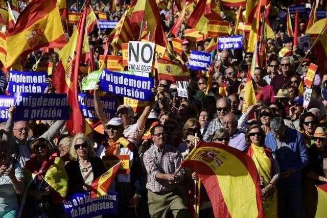 """La gente sostiene carteles que dicen """"No a la impunidad de golpistas"""" y """"(presidente regional catalán Carles) Puigdemont a prisión"""" mientras agita banderas españolas durante una manifestación llamando a la unidad en Plaza de Colón en Madrid el 28 de octubre de 2017, un día después se impuso el control directo sobre Cataluña en un intento por separarse de España. España se movió para afirmar el dominio directo sobre Cataluña, reemplazando a sus funcionarios ejecutivos y altos para sofocar un impulso de independencia que ha sumido al país en una crisis y ha puesto nerviosa a la Europa secesionista. / AFP PHOTO / JAVIER SORIANO"""
