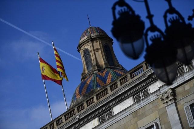 Las banderas española (L) y catalana Senyera revolotean sobre el Palacio de la Generalitat de Cataluña en Barcelona el 28 de octubre de 2017, un día después de que se impuso el control directo sobre la región en un intento por separarse de España. España se movió para afirmar el dominio directo sobre Cataluña, reemplazando a sus funcionarios ejecutivos y altos para sofocar un impulso de independencia que ha sumido al país en una crisis y ha puesto nerviosa a la Europa secesionista. / AFP PHOTO / PIERRE-PHILIPPE MARCOU