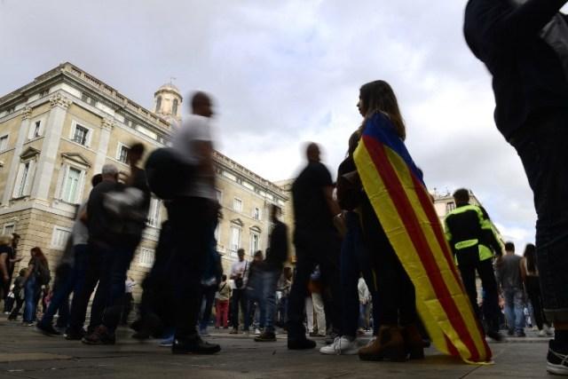 Una mujer envuelta con una bandera catalana de Estelada independentista se encuentra con otros en el Palacio de la Generalitat de Cataluña en Barcelona el 28 de octubre de 2017, un día después de que se impuso el control directo sobre la región en un intento por separarse de España. España se movió para afirmar el dominio directo sobre Cataluña, reemplazando a sus funcionarios ejecutivos y altos para sofocar un impulso de independencia que ha sumido al país en una crisis y ha puesto nerviosa a la Europa secesionista. / AFP PHOTO / PIERRE-PHILIPPE MARCOU