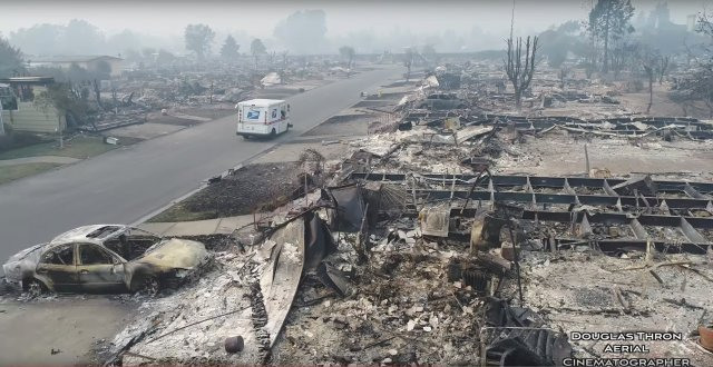 A postman delivers mail in fire-devastated Santa Rosa, California, United States October 10, 2017 is seen in this still images obtained from social media video. Douglas Thron/ via REUTERS  THIS IMAGE HAS BEEN SUPPLIED BY A THIRD PARTY. MANDATORY CREDIT. NO RESALES. NO ARCHIVES. MUST ON SCREEN COURTESY NAOTO YOSHIDOME  MUST NOT OBSCURE DOUGLAS THRON LOGO