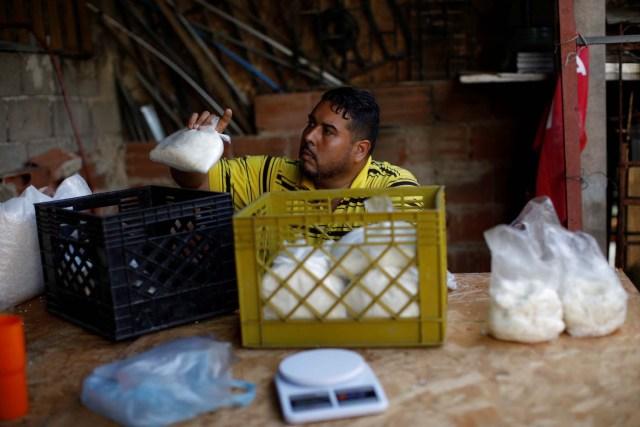 Medical equipment repairman Leandro Colmenares puts corn dough on plastic bags at the backyard of his house in Caracas, Venezuela October 3, 2017. Picture taken October 3, 2017. REUTERS/Carlos Garcia Rawlins
